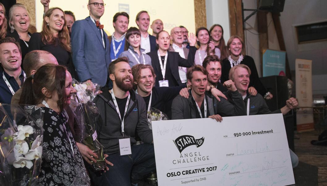 Gründerne fra Learnlink i front -- med pengepremien -- i etterkant av kåringen. I bakgrunnen og på siden sees gründere fra de andre startupene, og investorene som avgjorde hvem som skulle vinne. Foto: Benedicte Tandsæther-Andersen