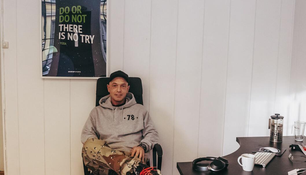 Gründeren bak Pindem, Ørjan Alexander Jenssen, sitter ved siden av en innrammet poster med Yodas kloke ord, som henger på veggen til daglig påminnelse.  Foto: Benedicte Tandsæther-Andersen