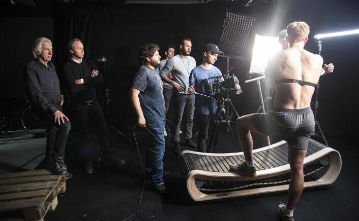 Arne Laugstøl og Håvard Bjor (t.v.) følger filminnspillingen, der landslagsroer Martin Helset løper med det nye pustebeltet deres. Foto: Per-Ivar Nikolaisen