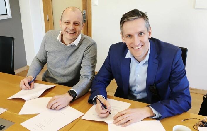 Pål Reinert Bredvei i Documaster og Christian Melby i Summa Equita signerer i forbindelse med storemisjonen i fjor. Foto: Documaster