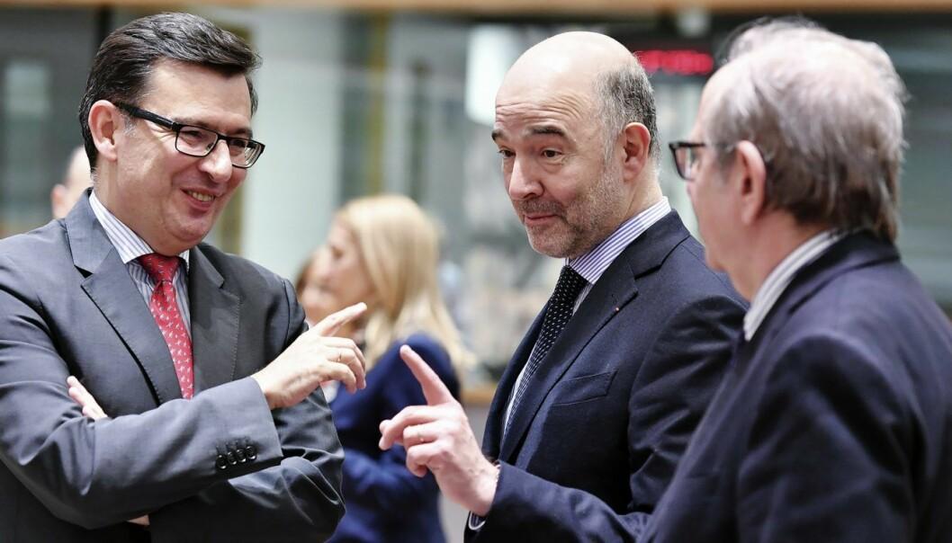 Den spanske nærings-  og konkurranseministeren Roman Escolano (i midten), snakker med EU-kommisær for økonomi og finans, Pierre Moscovici. Foto: AP Photo/Geert Vanden Wijngaert