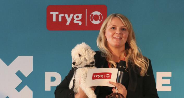 Kathrine Bjerga Tøraasen introduserer startupen Tracy -- som har laget en fitbit for hund -- mens hun holder en av brukerne deres på armen. Foto: Tryg Xplore