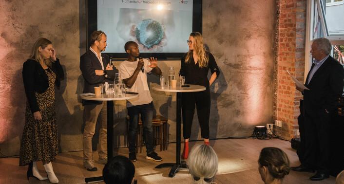 Olivier Mukuta (Vipicash) svarer på et av konferansier Christian Borch sine spørsmål, mens (fra venstre til høyre) Marit Glad (sjef for utviklingsprosjekter og innovasjonseenheten hos Flyktninghjelpen), Lars André Skari (utenlandssjef for Røde Kors) og Thea Sommerseth Myhren (Diwala) hører på. Foto: Benedicte Tandsæther-Andersen