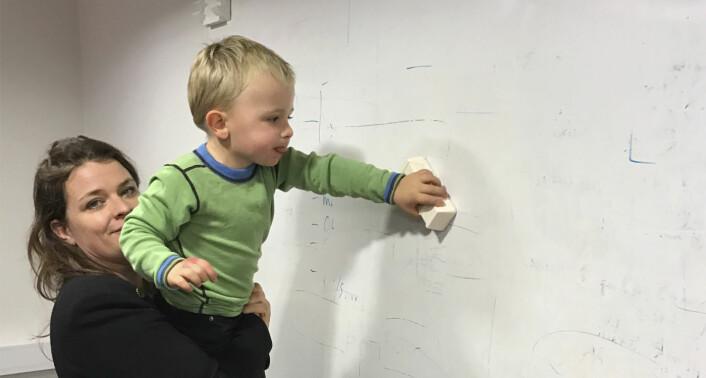Åste holder sønnen, som hvisker ut notatene på en whiteboard. Foto: Privat