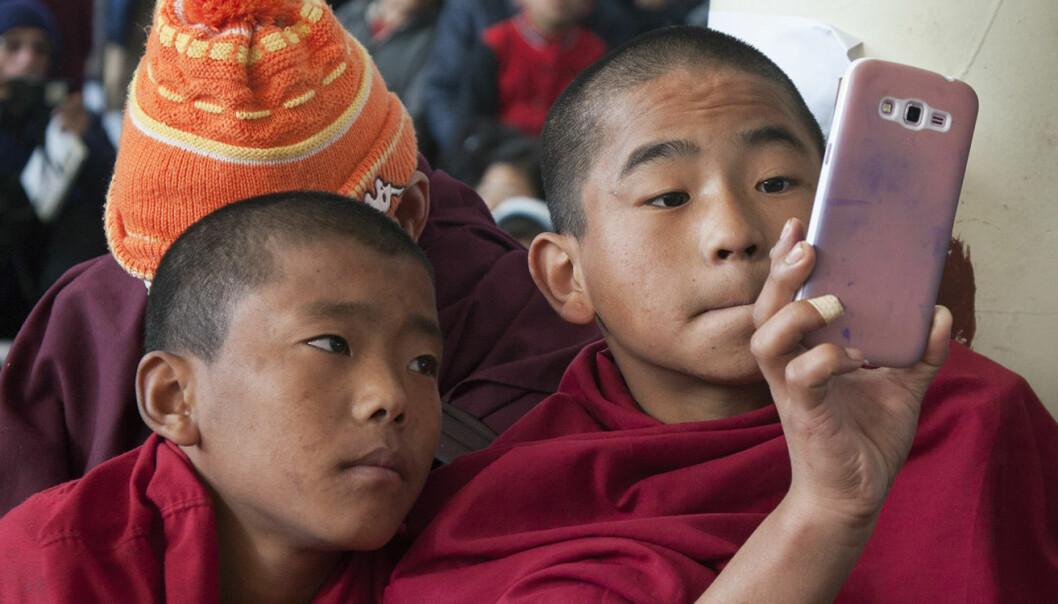 En ung buddhistmunk i eksil bruker et mobilkamera for å forevige 25-årsmarkeringen av at buddhistenes spirituelle leder, Dalai Lama fikk Nobels fredspris. Interne politiske konflikter og anklager om etnisk rensing preger fortsatt Myanmar. Foto: AP Photo/Ashwini Bhatia