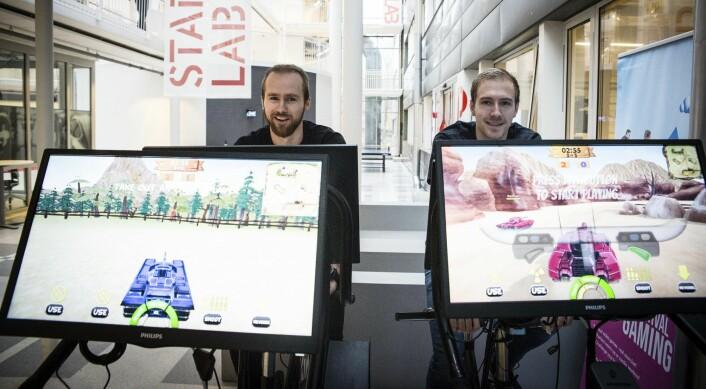 Erling Magnus Solheim og Stian Weie i Playpuls spiller tanks mot tanks på spinningsyklene utenfor StartupLab. Foto: Per-Ivar Nikolaisen