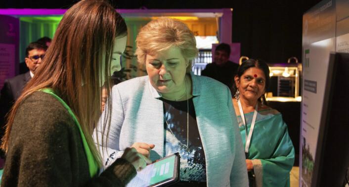 Empowers kommunikasjons- og mediaansvarlige, Anette Simonsen, viser statsminister Erna Solberg hvordan Empowers tjeneste fungerer. Her fotografert i forbindelse med at Empower hadde stand på Xyneto Limited. Foto: Empower