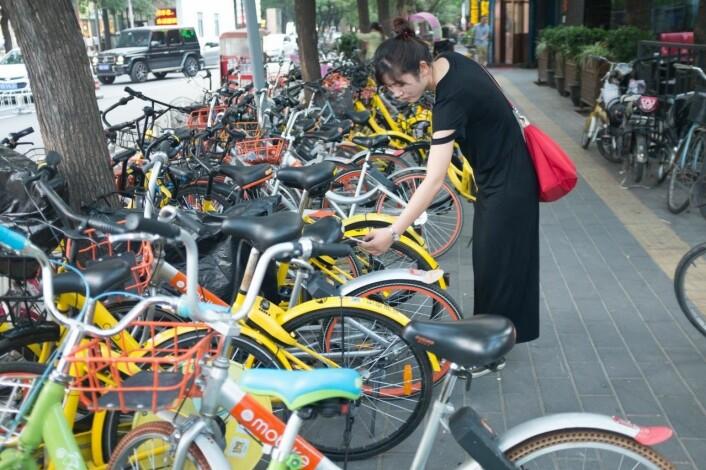 En kinesisk kvinne leier en sykkel ved å skanne en QR-kode før -- og etter -- sykkelturen.