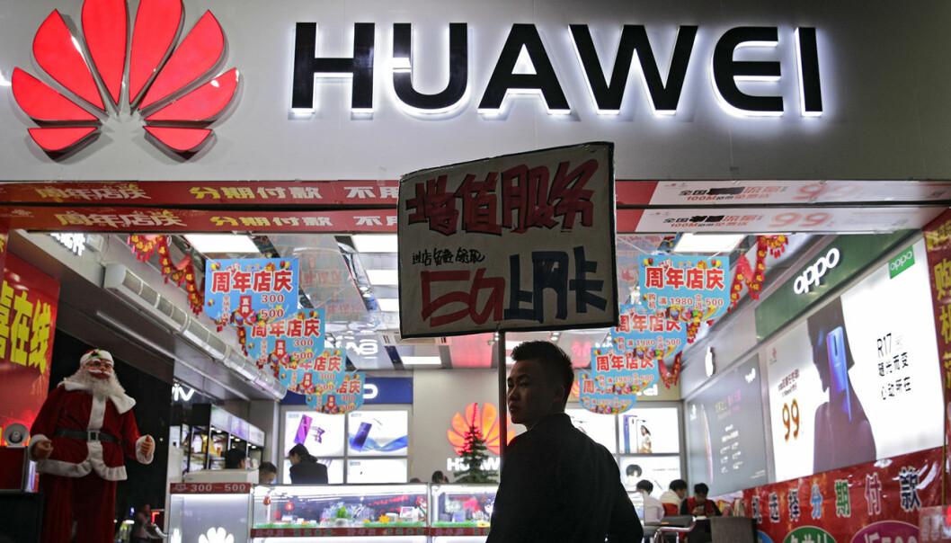 En ansatt holder et skilt med reklame for Huawei 5G-internettjenester, utenfor en mobilbutikk i Shenzhen i det sørlige Kinas Guangdong province. Foto: AP Photo/Andy Wong
