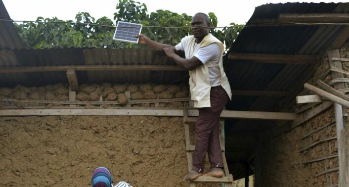 En av Wattero sine kunder i Godjiboue viser frem solcellene han har på taket av huset sitt. Foto: Wattero